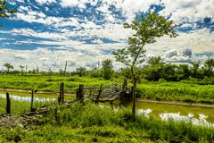 Rural Crossings. A old wooden bridge over a slow flowing river with lush greenery and blue skies and puffy clouds Royalty Free Stock Photography
