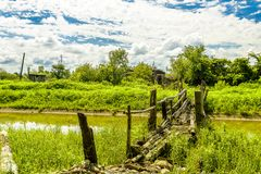 Rural Crossings. A old wooden bridge over a slow flowing river with lush greenery and blue skies and puffy clouds Stock Photo