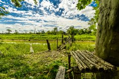 Rural Crossings. A old wooden bridge over a slow flowing river with lush greenery and blue skies and puffy clouds Royalty Free Stock Image