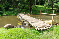 Old wooden bridge over the stream with green lawn Royalty Free Stock Images