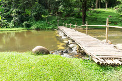 Old wooden bridge over the stream with green lawn Royalty Free Stock Photo