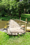 Old wooden bridge over the stream with green lawn Royalty Free Stock Photography