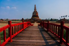 Old Wooden bridge with Red Handrails heading to Ancient Pagoda in Ayutthaya City, Thailand. Wat Pradu Songtham Ayutthaya is a historical landmark in Thailand stock images