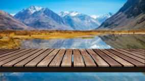 Old wooden bridge on the reflection of Blur snow mountains Stock Image