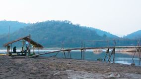 The old wooden bridge on the river. Laos, Luang Prabang, evening Stock Images