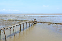 Old wooden bridge into the sea stock images