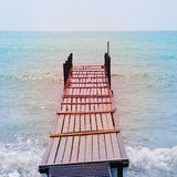Old wooden bridge in the sea in a retro style Royalty Free Stock Images