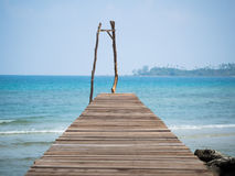 Old wooden Bridge to the blue sea Stock Image