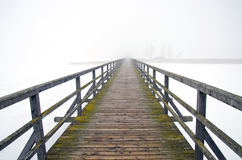 Old wooden bridge in winter morning fog Stock Photo