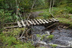 Old wooden bridge. Old and worn wooden bridge crossing a small creek in Norway Stock Image