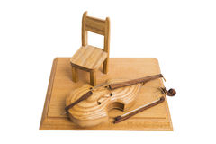Old wooden broken violin on stand with chair on isolated background. Royalty Free Stock Photo