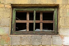 A small window with broken pieces of glass on a brick wall stock images