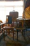 Old brown chairs and a suitcase on the table stock images