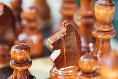 Old Wooden Brown Chess Knight and Pawns Standing On Chessboard Royalty Free Stock Photos
