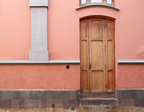 Old wooden brown door in a pink painted spanish house Royalty Free Stock Photos