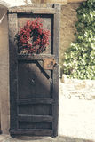 Old wooden brown door with red crown decoration Royalty Free Stock Photography