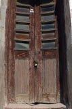 Old wooden brown door in ruin Stock Images