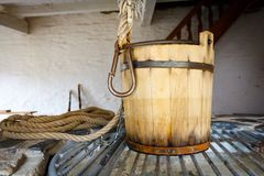 Old wooden bucket on a fountain in a historic farm stock photo