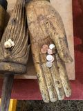 Old wooden Buddha hand with little one thai baht money coins inside, offerings and donation buddhist symbol. Ancient buddha hand royalty free stock images