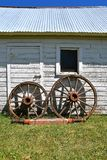 Old wooden buggy wheels. Wooden buggy wheels leaning against an old white shed with a metal roof Royalty Free Stock Photo
