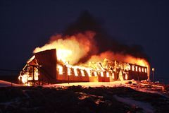 The old, wooden building of the arctic station is set on fire. Night. The station is on fire. stock photos