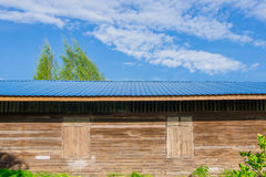 The old wooden building roofed with blue sheet metal roofs . Stock Photo