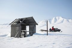 Old wooden building, snowmobile, Spitsbergen Royalty Free Stock Photo