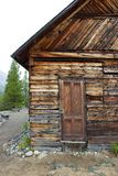 Old wooden building in Yukon, Canada. An old wooden building with a door on a cloudy day in the Yukon Territory. The woodwork has patterned details and shows Royalty Free Stock Photos