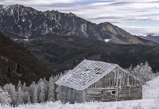 Old wooden cabin in the winter mountains lanscape. An old abandoned sheepfold covered in snow in the beginning of winter Royalty Free Stock Photography