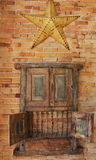 Old Wooden Cabinet and Metal Country Star. Old rustic wooden cabinet hanging on a brick wall, with opened lower doors showing bars and yellow metal country star Royalty Free Stock Image