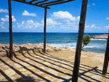 Old wooden canopy on the sea coast and blue sky Royalty Free Stock Photos