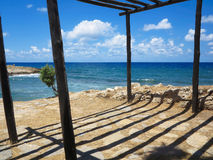 Old wooden canopy on the sea coast and blue sky Stock Photos