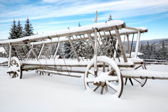Old wooden carriage in snow on winter meadow Stock Images