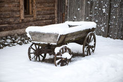 Old wooden cart in the courtyard peasant Estonian villages in winter in the snow. Royalty Free Stock Photography