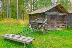 Old wooden cart in front of log barn Stock Image