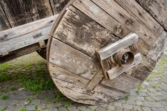 Old wooden cart with a stone masonry wall on the background with a cartiera sign paper mill in Italian language. royalty free stock photos