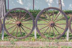 Old wooden cartwheel is fence for farm. Royalty Free Stock Photo