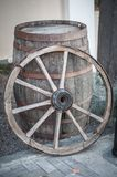 An old wooden cartwheel stands by a wooden barrel stock image