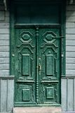 Old wooden carved door bells painted with green oil paint with bronze handle and steel lock royalty free stock photo
