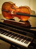 Old wooden Cello and bow on grand piano with cream background royalty free stock photos
