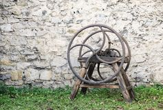 Old wooden chaff cutter. Standing on grass in front of stone wall Royalty Free Stock Photography