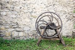 Old wooden chaff cutter. Standing on grass in front of stone wall Stock Image