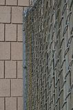 A old wooden chain linked fence running into a wall. Along the old steel and wooden metal chain linked fence in the back warehouse area running into the wall stock image