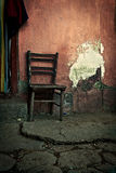 Old wooden chair. Located in the old house's yard, next to a brick wall Stock Photo