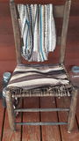 An old wooden chair. Background. With rugs hanging on it. And mason jars beside it Royalty Free Stock Photography