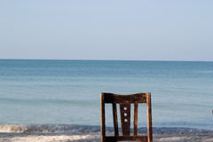 Old wooden chair at beachfront Stock Photos