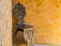 Old wooden chair chiseled. Old wooden chair in a corner royalty free stock photo
