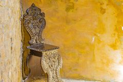 Old wooden chair chiseled. Old wooden chair in a corner stock images