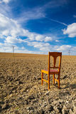 Old wooden chair on the empty field Stock Photo