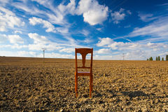 Old wooden chair on the empty field Stock Photos